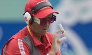 Canada's Susan Nattrass, from Edmonton, knocks away ejecting cartridges as she competes in the women's trap qualification at the Beijing Olympics in Beijing, China Monday Aug.11, 2008. THE CANADIAN PRESS/Adrian Wyld